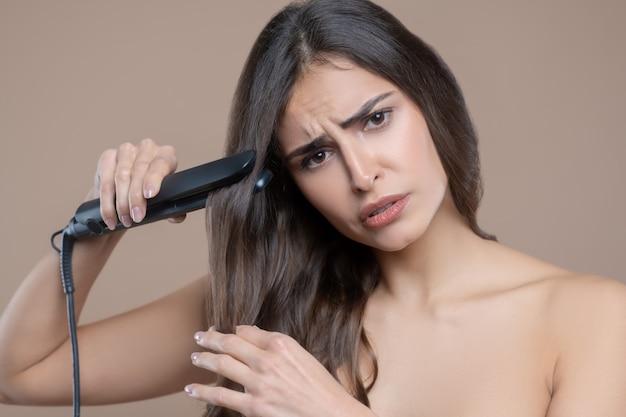 Umore triste. triste bella donna dai capelli lunghi con spalle nude e piastra per capelli lisciatura arricciatura