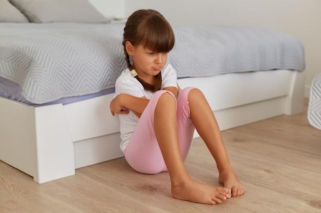Bambina triste e offesa seduta al letto con le labbra imbronciate, offesa da amici o genitori, che esprime tristezza, bambino che indossa una maglietta bianca e pantaloncini rosa.