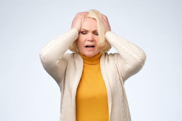 Donna maggiore anziana triste che guarda giù e piange