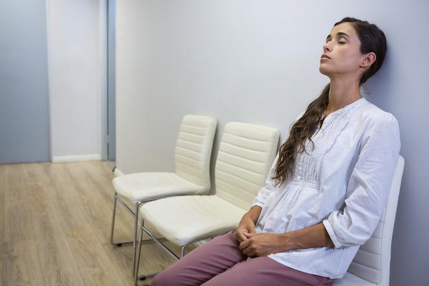Paziente triste con gli occhi chiusi che si siede sulla sedia all'ospedale