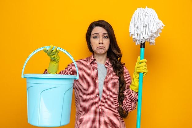Donna delle pulizie piuttosto caucasica triste con guanti di gomma che tengono secchio e mocio