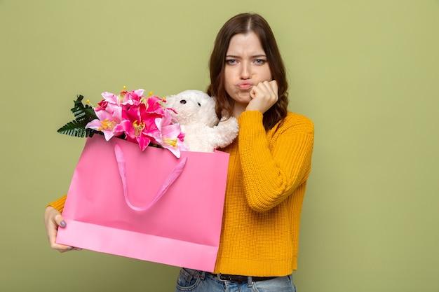Triste mettendo la mano sulla guancia bella ragazza che tiene il sacchetto del regalo