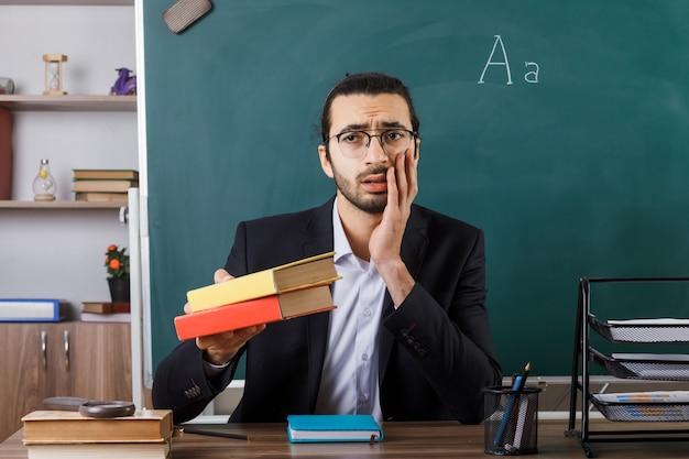 Triste mettendo la mano sulla guancia insegnante maschio con gli occhiali che tiene fuori il libro in telecamera seduto al tavolo con gli strumenti della scuola in classe