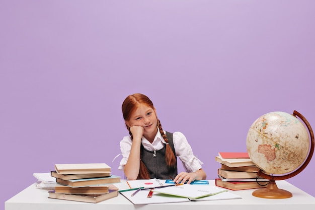 Scolaretta adorabile dai capelli rossi triste con le lentiggini e le trecce in vestiti scolastici che guardano davanti sul muro isolato lilla