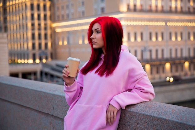 Adolescente dai capelli rossi triste in felpa con cappuccio rosa la sera sulla strada della città illuminata.