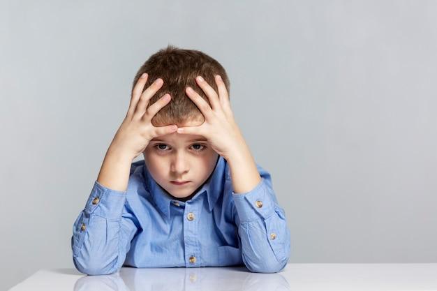 Il ragazzo triste dello scolaro si siede al tavolo e tiene la sua testa