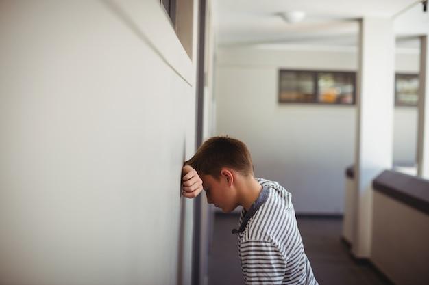 Scolaro triste che si appoggia la testa contro il muro in corridoio