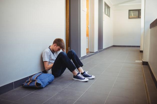 Scolaro triste che si siede nel corridoio