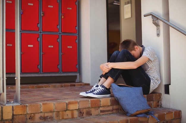Scolaro triste che si siede sulla scala