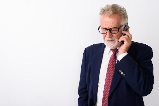 Uomo d'affari barbuto anziano triste pensare mentre guarda verso il basso e parla al telefono cellulare su bianco
