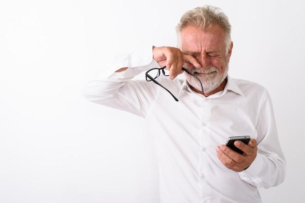Uomo barbuto anziano triste utilizzando il telefono cellulare mentre piange e tiene gli occhiali su bianco