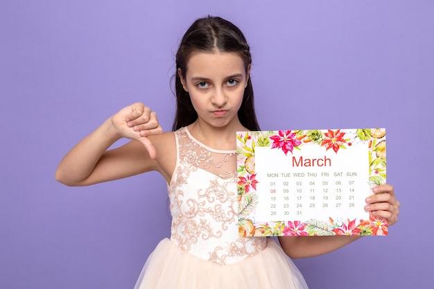 Triste che mostra il pollice verso il basso bella bambina il giorno della donna felice che tiene il calendario