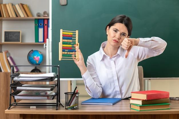 Triste che mostra il pollice verso il basso giovane insegnante femminile seduta al tavolo con gli strumenti della scuola che tengono l'abaco in aula