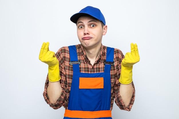 Triste gesto di punta che mostra il giovane addetto alle pulizie che indossa l'uniforme e il berretto con i guanti
