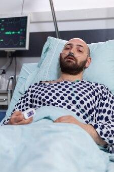 Uomo malato triste con tubo dell'ossigeno nasale che riposa in cattive condizioni guardando la telecamera durante il recupero respiratorio nel reparto ospedaliero