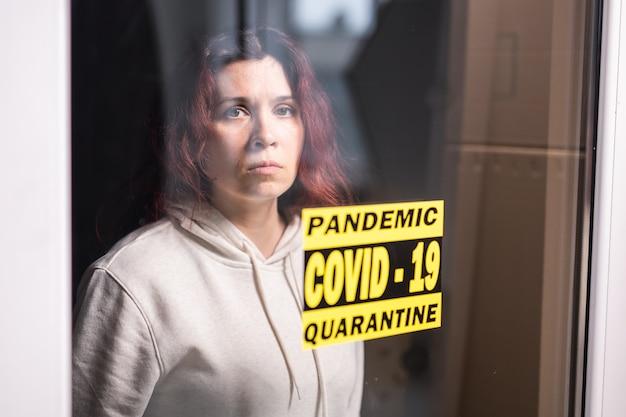 Donna triste e malata di virus corona che guarda attraverso la finestra