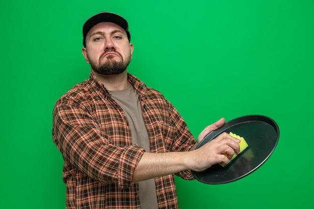 Uomo delle pulizie slavo triste che pulisce i piatti con la spugna