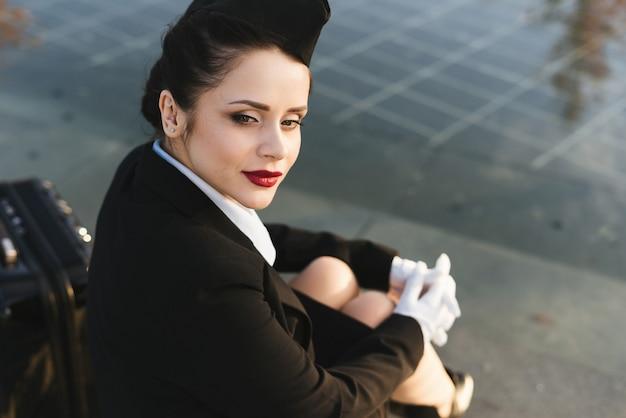 La donna triste dell'hostess in uniforme si siede sui gradini