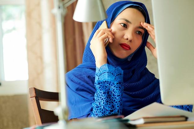 Donna musulmana sollecitata triste che rivolge al telefono