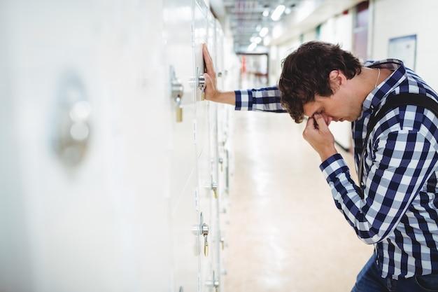 Studente triste che si appoggia sull'armadietto