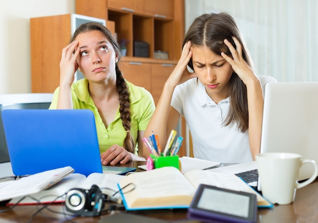 Studenti tristi che studiano a casa