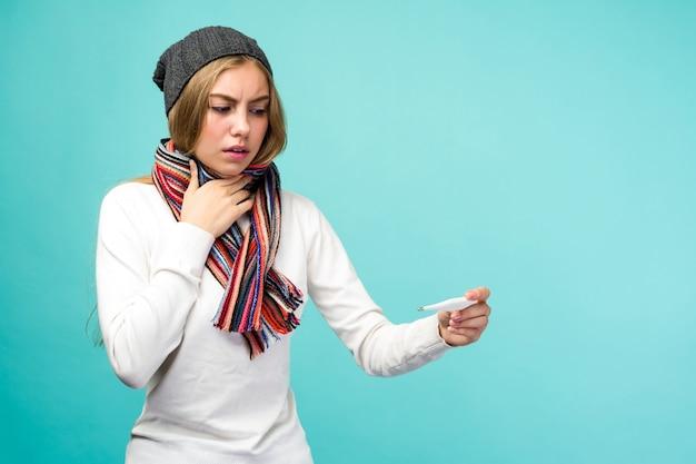 Triste ragazza adolescente avente canna fumaria tenendo termometro su sfondo blu