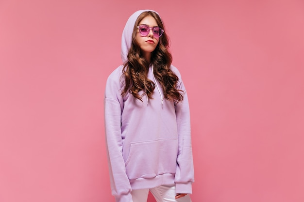 La ragazza teenager triste in felpa con cappuccio viola esamina la macchina fotografica