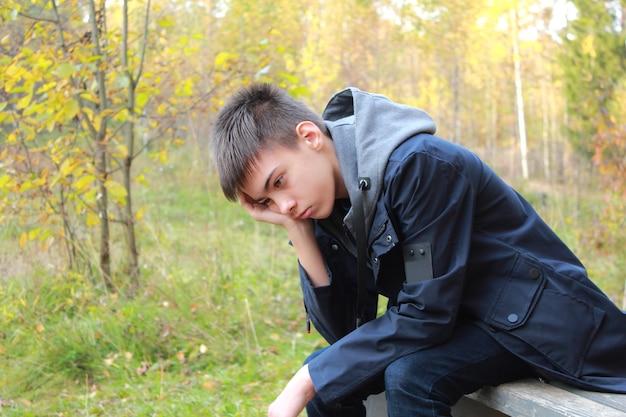 Triste ragazzo adolescente seduto su una panchina in un parco in autunno