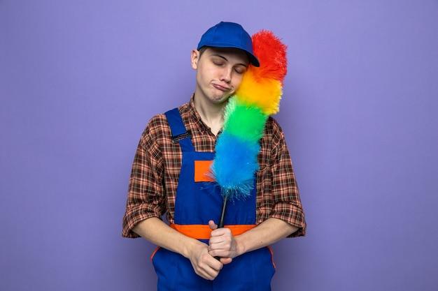Giovane ragazzo delle pulizie con la testa inclinata triste che indossa l'uniforme e il berretto che tiene pipidastre