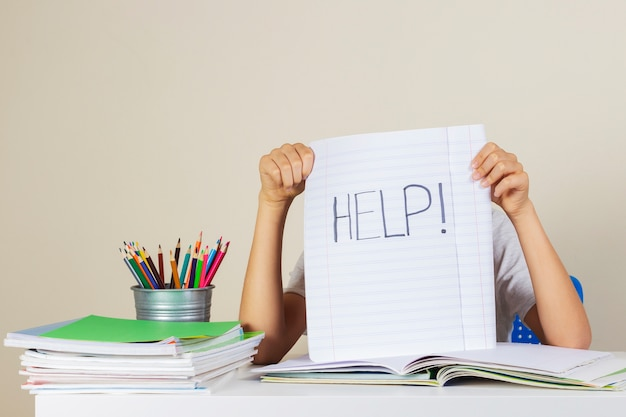 Il ragazzo stanco triste ha bisogno di aiuto con i compiti a casa