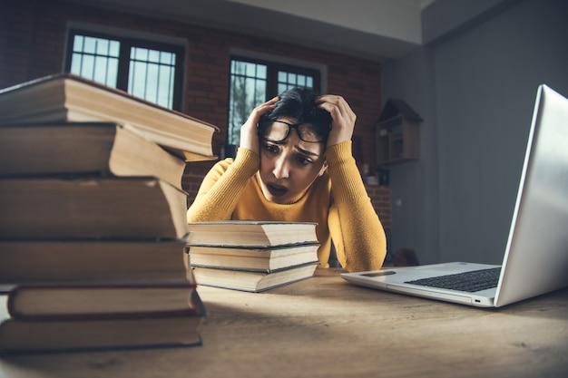 Libri e computer della mano della donna triste e stanca sul tavolo