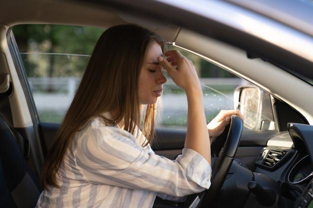 Triste e stanca giovane donna alla guida di un'auto ragazza infelice autista depresso e ansioso tenere il volante