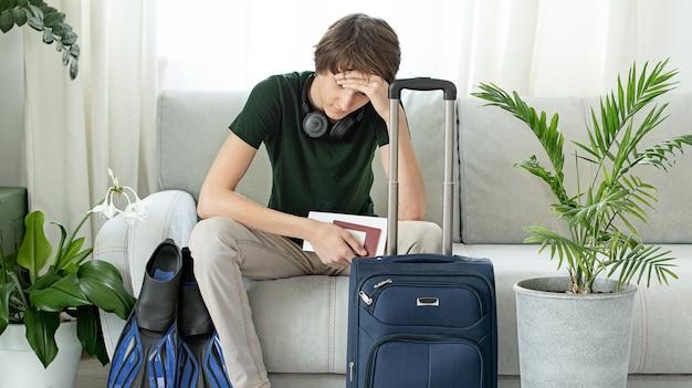 Un adolescente turistico triste con una valigia e le pinne rimane a casa durante la pandemia di coronavirus. annullamento delle ferie e chiusura delle frontiere tra i paesi. cancellazione del volo