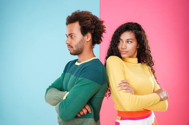 Triste infelice giovane coppia africana in piedi con le braccia incrociate