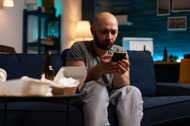 Uomo triste infelice disperato ansia scioccato che naviga sullo smartphone