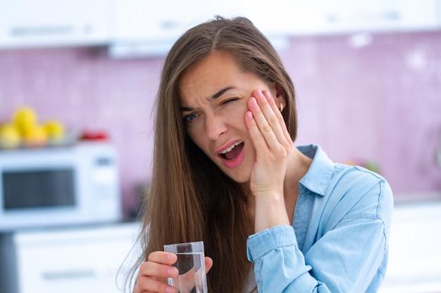 Giovane donna infelice triste che soffre di mal di denti a casa. dolori ai denti e problemi ai denti