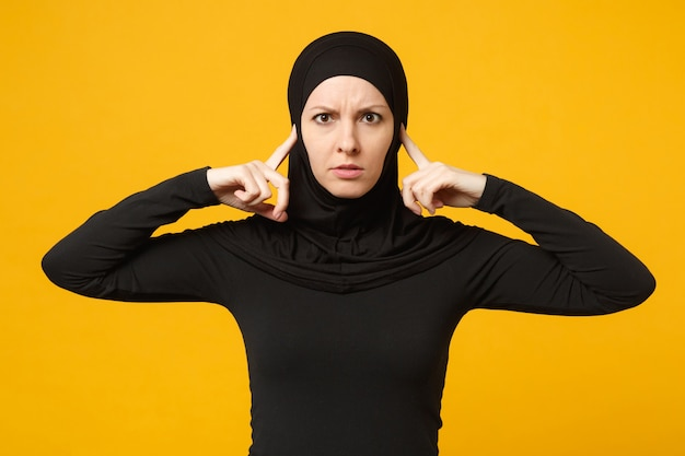 Triste sconvolto pianto confuso giovane donna musulmana araba in abiti neri hijab in posa isolata sulla parete gialla, ritratto. concetto di stile di vita dell'islam religioso della gente.