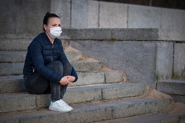 Ragazza depressa arrabbiata triste, giovane donna frustrata sola che si siede sulle scale, sofferente a causa dell'isolamento, coronavirus. persona in maschera protettiva medica sul viso. cuore spezzato, virus, concetto di epidemia