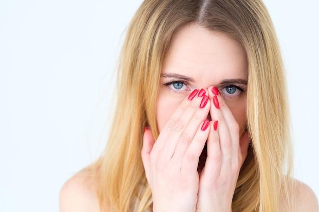 Donna triste sconvolta che copre il viso con le mani sul muro bianco.
