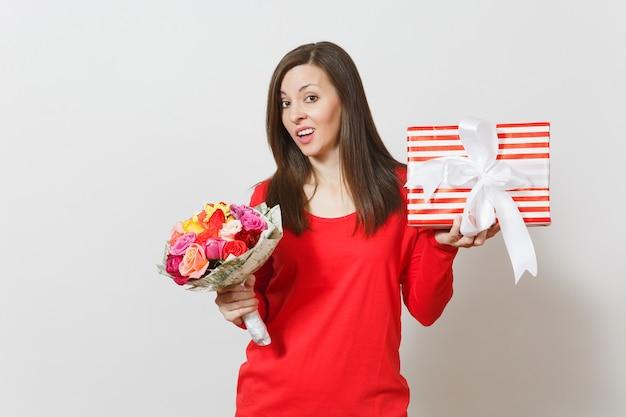 Donna turbata triste in vestiti rossi che tengono il mazzo di bei fiori delle rose, scatola attuale con il regalo isolato su fondo bianco. san valentino, concetto di festa di compleanno della giornata internazionale della donna.