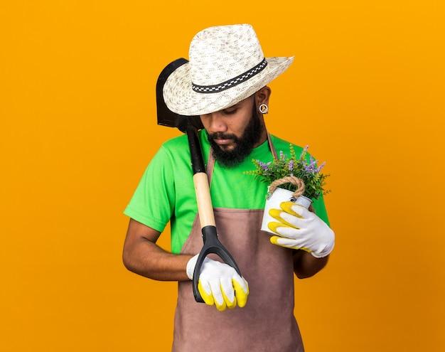 Triste con la testa abbassata giovane giardiniere ragazzo afroamericano che indossa cappello e guanti da giardinaggio che tengono vanga con fiore in vaso di fiori isolato sulla parete arancione