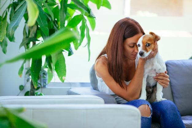 Donna triste in un divano con un cucciolo malato