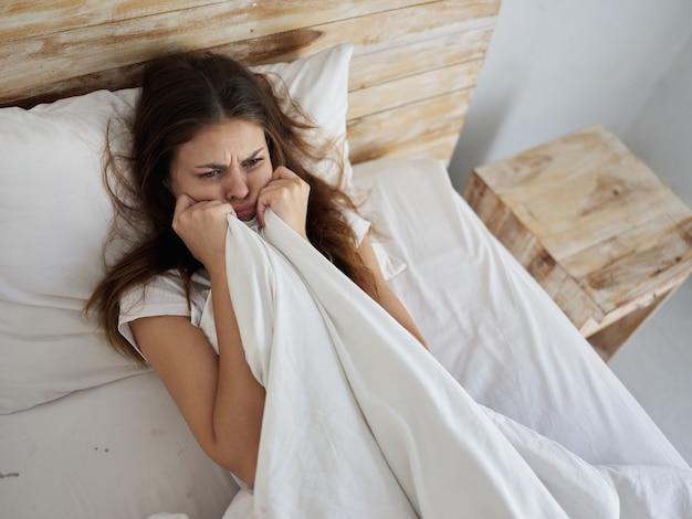 Donna triste che tiene una coperta a letto mattina
