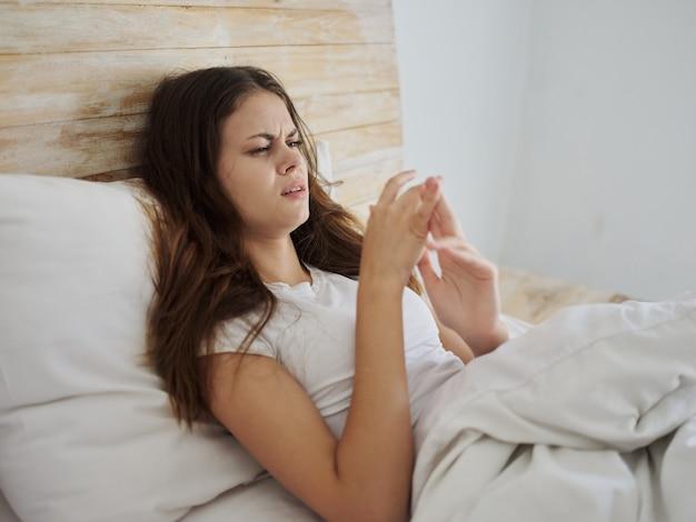 La donna triste giace a letto con problemi di salute di temperatura