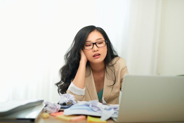 Donna triste che guarda il computer portatile che tocca la testa avendo problemi al lavoro seduto in un ufficio moderno