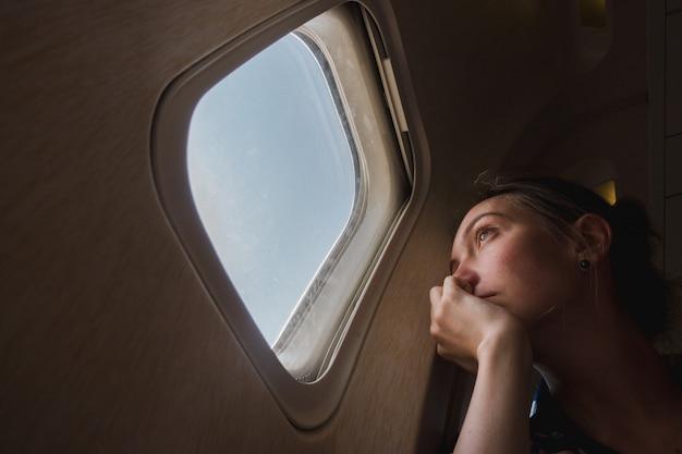 Donna triste all'oblò in aereo