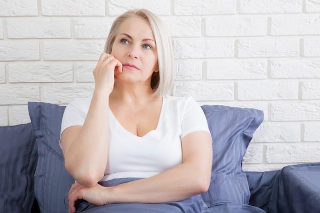 Triste donna seduta sul letto al mattino. menopausa depressa