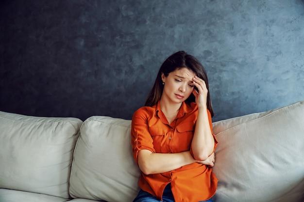 Triste donna seduta sul divano e tenendo la testa. la solitudine è il peggior nemico.