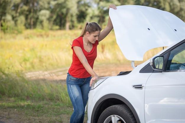 Donna triste in piedi davanti a un'auto rotta sul ciglio della strada