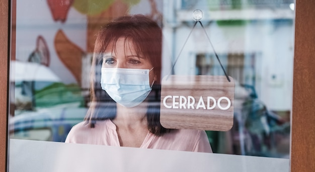 Donna triste con maschera facciale cambiando aperto a chiuso segno in spagnolo sulla finestra